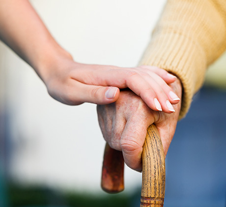 man holding cane with woman's hand on his