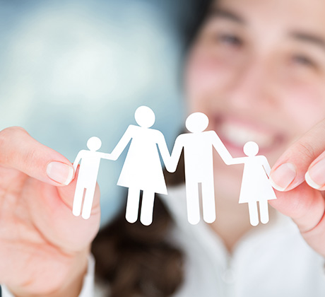 a woman holding a paper cutout of a family